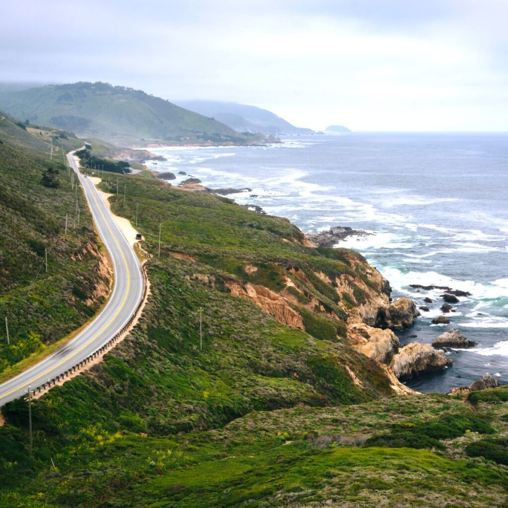 view of paved road next to cliffs by the ocean