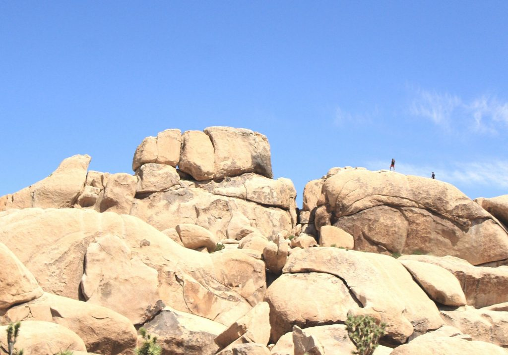 large rock with tiny climbers at the top in front of a blue sky