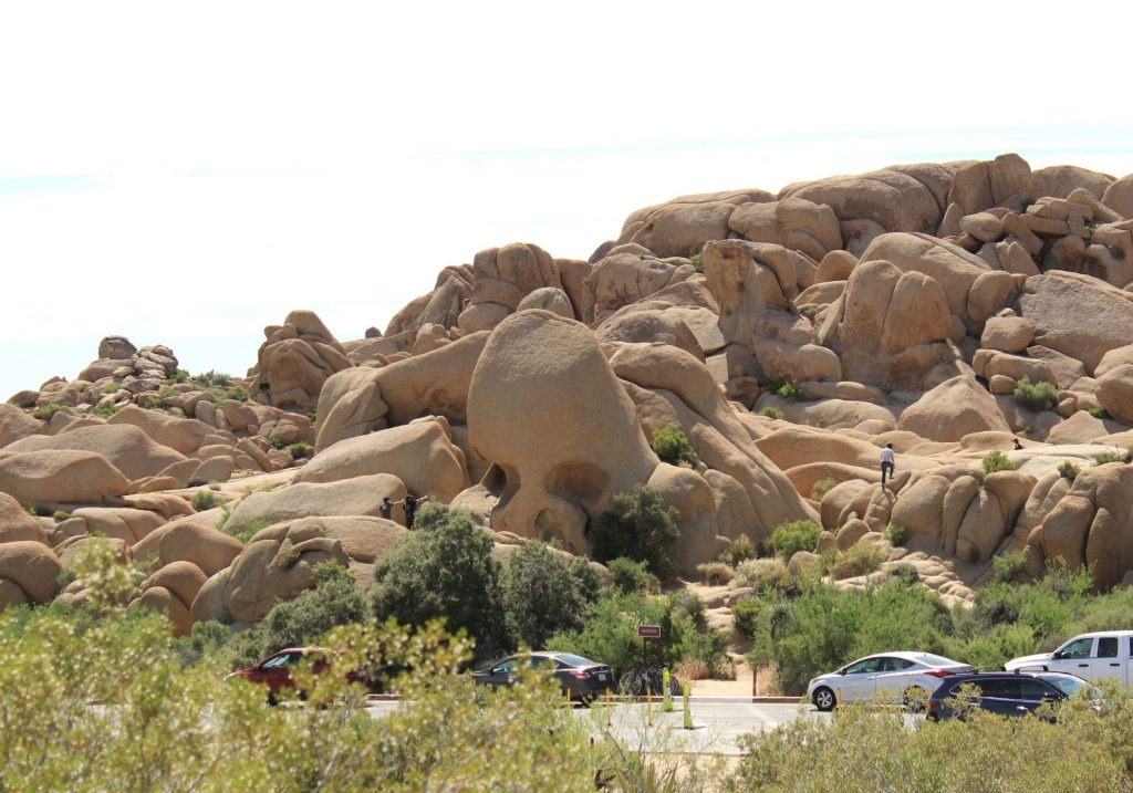Rock formation that looks like a human skull with giant boulders all around it and view of cars and road in front of it