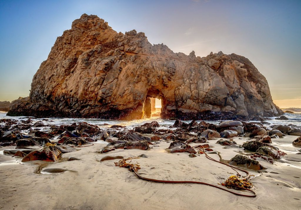 large rock formation with sun coming through at the beach