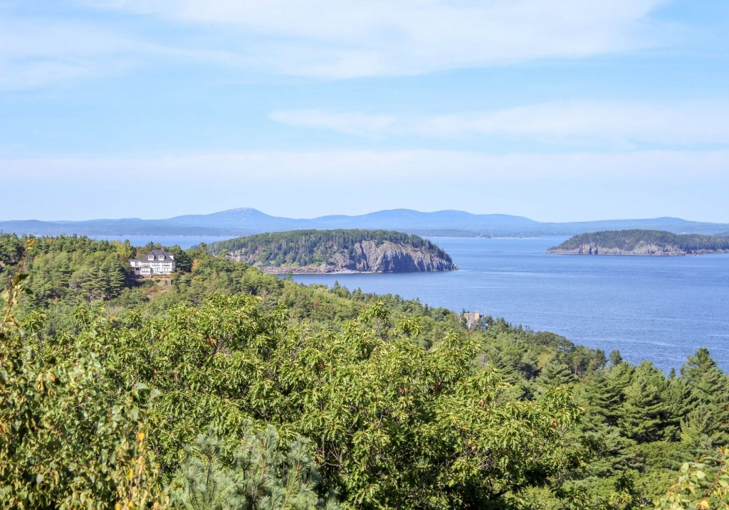 View of islands and water and trees with house in background at Acadia National Park