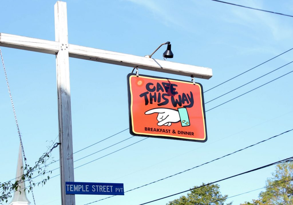 "Sign that says ""Cafe This Way"" and above street sign for Temple Street PVT"
