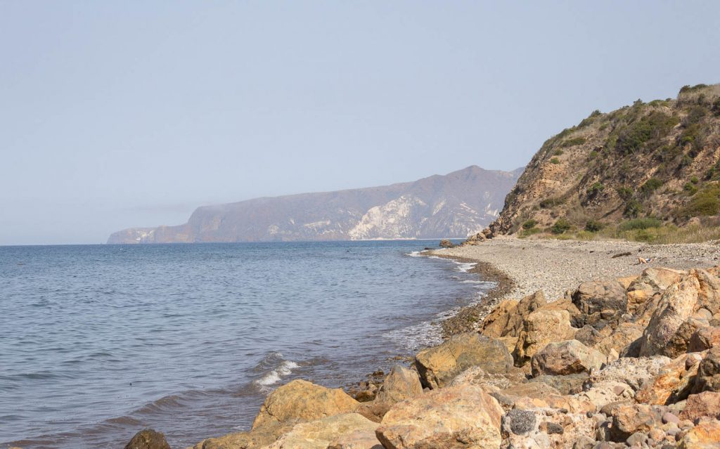 view of rocky beach with cliffs in the background