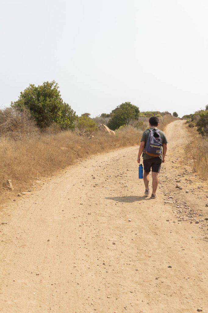 man walking on gravel road