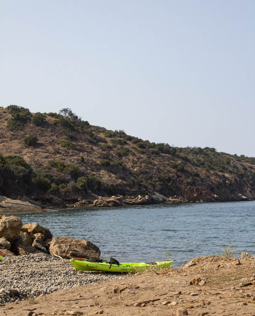 kayak at the rocky beach with hill in the background