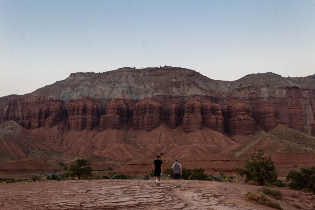 two men walk towards a large rock structure at Capitol Reef National Park