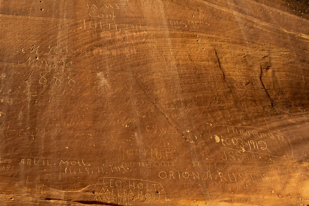 names and dates carved into the rock face at the Capitol Reef National Park pioneer register